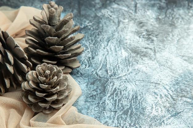 Vista inferior de pinhas em xale bege em superfície escura com espaço de cópia