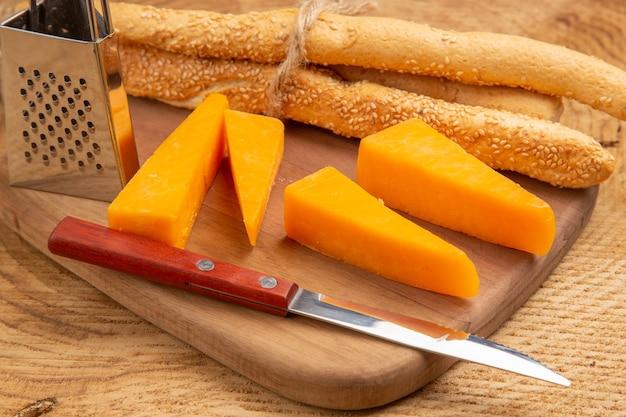 Vista inferior de queijo e faca de pão pequeno ralador na tábua de corte na superfície de madeira