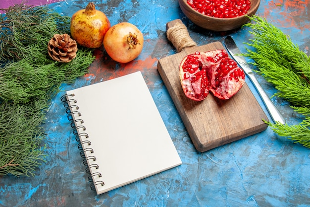 Vista inferior de sementes de romã em uma tigela faca de jantar uma romã cortada em uma tábua de cortar um caderno galhos de árvore no fundo azul
