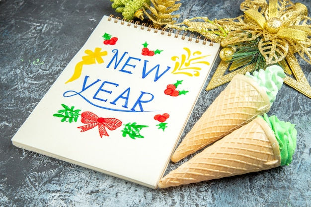 Vista inferior de sorvetes de ano novo escritos em enfeites de natal do bloco de notas em fundo cinza