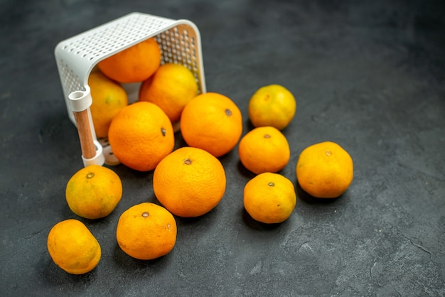 Vista inferior de tangerinas e laranjas espalhadas de uma cesta de plástico em fundo escuro