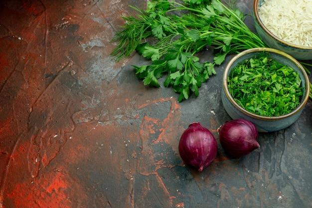 Vista inferior de tigelas com cebolinhas verdes picadas, salsa, arroz, cebola vermelha, mesa vermelha escura com espaço de cópia