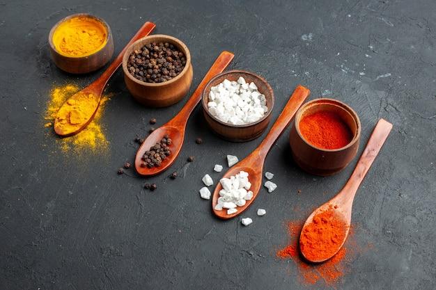 Vista inferior de tigelas com cúrcuma pimenta preta sae sal pimenta vermelha em pó colheres de madeira na mesa preta