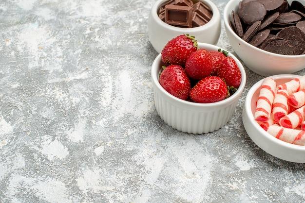 Vista inferior de tigelas com doces de morangos e chocolates no canto superior direito do fundo branco-acinzentado