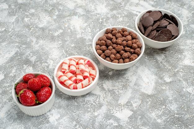 Vista inferior de tigelas com filas diagonais com morangos, doces e chocolates de cereais no fundo cinza-branco