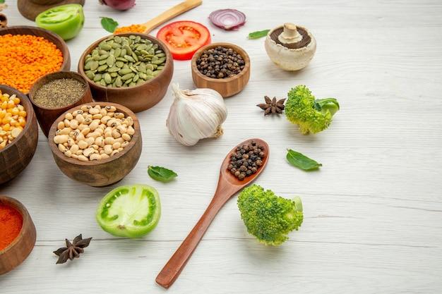 Vista inferior de tigelas com sementes de feijão, colheres de madeira, cogumelo de brócolis na mesa cinza
