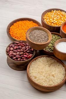 Vista inferior de tigelas de madeira com feijão arroz pimenta preta sementes de abóbora cúrcuma sal e lentilhas na mesa cinza