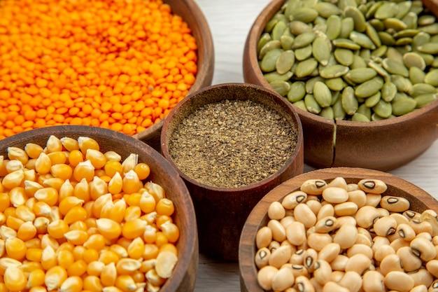 Vista inferior de tigelas de madeira com sementes de milho, feijão, sementes de abóbora, lentilhas, tigela de pimenta preta