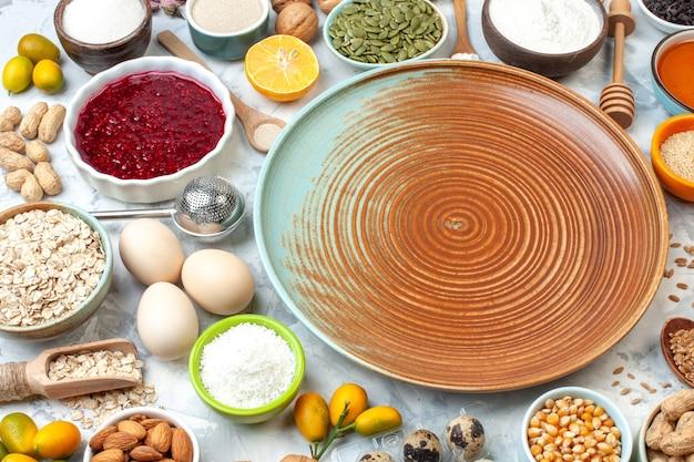Vista inferior de tigelas de prato redondo com sementes de milho geléia farinha de aveia pó de coco sementes de abóbora ovos cumcuats