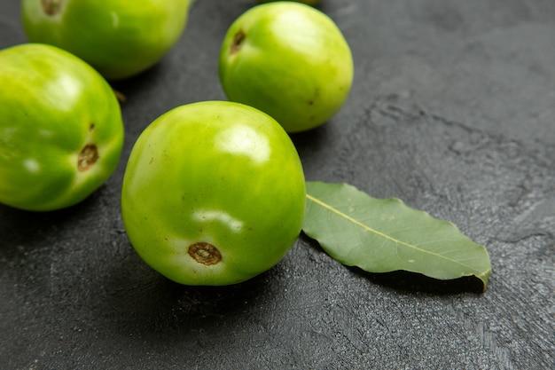 Vista inferior de tomates verdes e folha de louro em fundo escuro