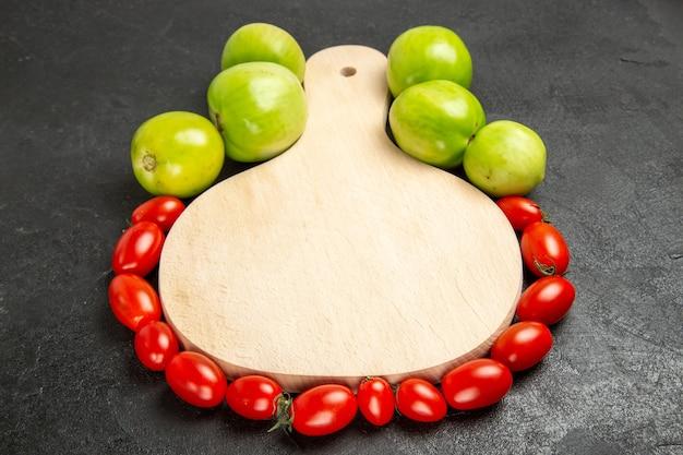 Vista inferior de tomates verdes e vermelhos ao redor de uma tábua de cortar em fundo escuro
