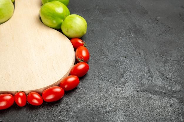 Vista inferior de tomates verdes e vermelhos ao redor de uma tábua em fundo escuro