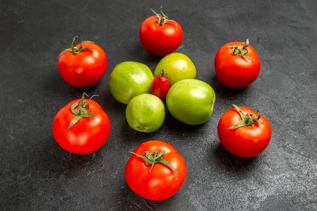 Vista inferior de tomates vermelhos e verdes ao redor de um tomate cereja em fundo escuro