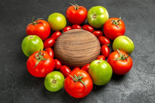 Vista inferior de tomates vermelhos e verdes cereja em torno de uma placa de madeira em solo escuro