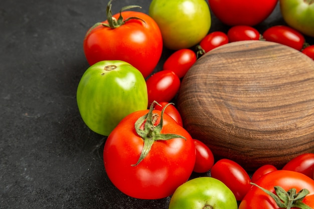 Vista inferior de tomates vermelhos e verdes cereja em volta de uma placa de madeira em fundo escuro