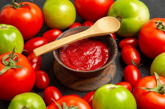 Vista inferior de tomates vermelhos e verdes em volta de uma tigela com ketchup e uma colher de pau em fundo escuro