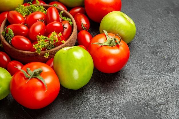Vista inferior de tomates vermelhos e verdes em volta de uma tigela com tomates cereja e flores de endro em fundo escuro