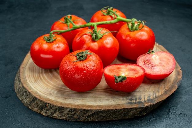 Vista inferior de tomates vermelhos em uma placa de madeira na mesa escura