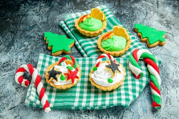 Vista inferior de tortinhas de natal pequenas, doces de natal na toalha de mesa quadriculada branca verde na mesa cinza