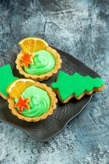 Vista inferior de tortinhas pequenas com biscoitos de natal de creme verde em placa preta na superfície cinza