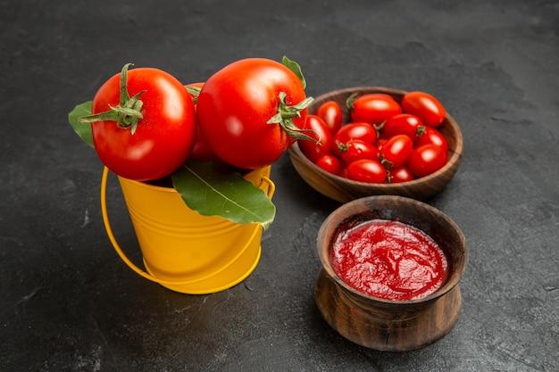 Vista inferior de um balde com tigelas de tomate com tomate cereja e ketchup em fundo escuro
