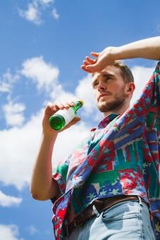 Vista inferior de um homem elegante com uma garrafa