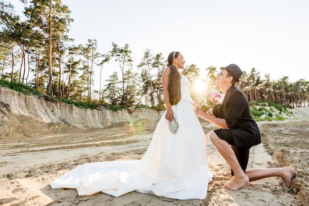 Vista inferior de um jovem positivo ajoelhado em frente à sua encantadora noiva