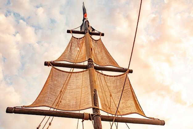 Vista inferior de um mastro de navio com velas bege