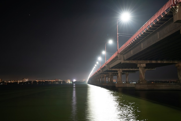 Vista inferior de uma bela e longa ponte brilhante com luzes frias e carros velozes sobre o grande e belo rio dnieper em dnepropetrovsk, na bela ucrânia