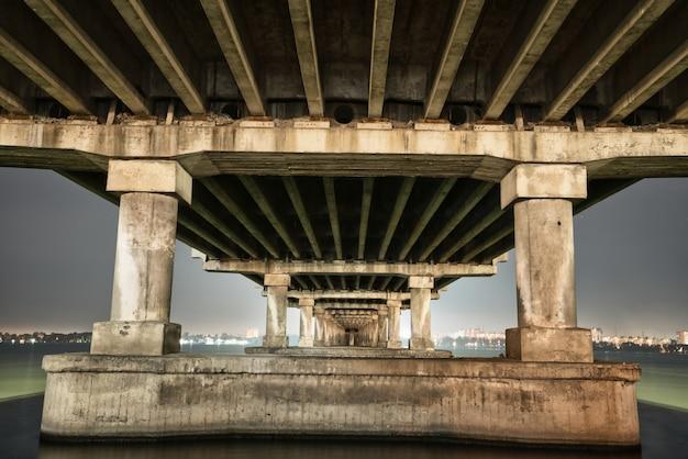 Vista inferior de uma bela e longa ponte sobre o grande e belo rio dnieper
