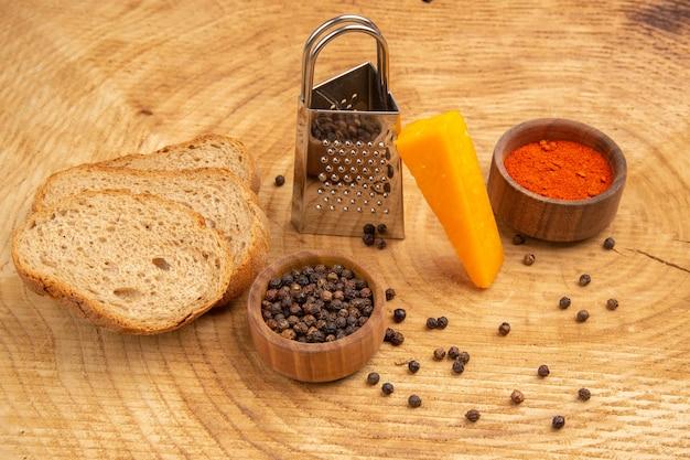 Vista inferior de uma fatia de queijo espalhado ralador de pimenta-do-reino especiarias diferentes em pequenas tigelas fatias de pão na superfície de madeira