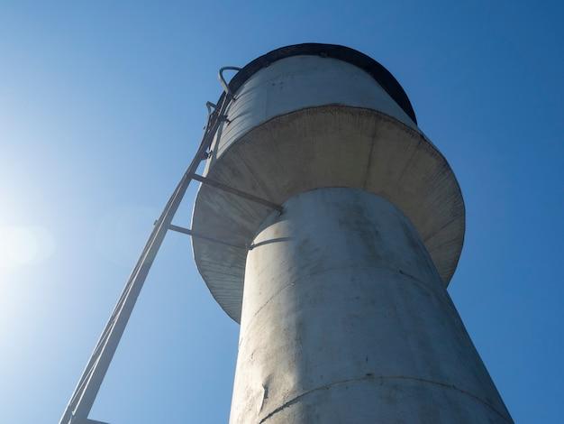Vista inferior de uma velha torre de água de metal em um dia ensolarado no campo russo no verão.