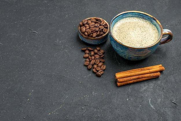 Vista inferior de uma xícara de café com sementes de café em paus de canela no fundo escuro isolado