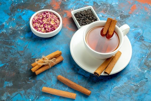 Vista inferior de uma xícara de chá com canela de diferentes ingredientes em pequenas tigelas na superfície azul vermelha