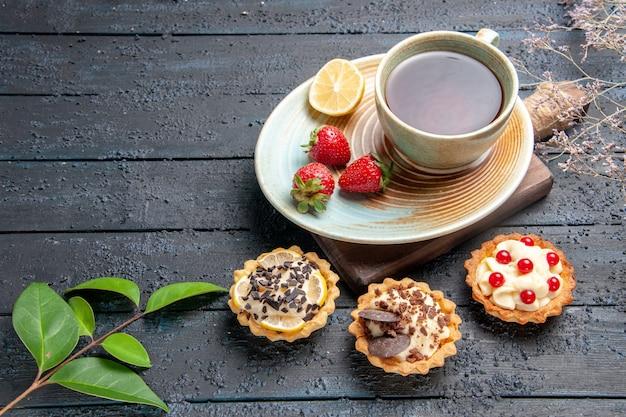 Vista inferior de uma xícara de chá com fatia de limão e morangos em tortas de pires folhas de canela secas de laranja na mesa de madeira escura
