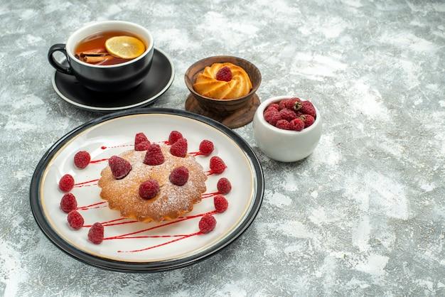 Vista inferior de uma xícara de chá com rodelas de limão e bolo de baga de canela em um biscoito de prato oval na superfície cinza copie o local