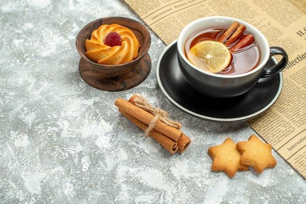 Vista inferior de uma xícara de chá com rodelas de limão e paus de canela em biscoitos de jornal na superfície cinza