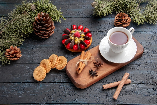 Vista inferior de uma xícara de chá de sementes de anis e canela no prato de servir de madeira, bolo de baga de pinhas e biscoitos diferentes em fundo escuro