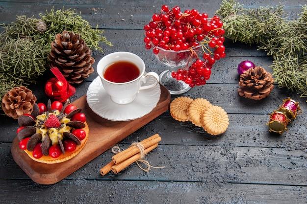 Vista inferior de uma xícara de chá e bolo de frutas vermelhas no prato de servir de madeira groselha em um vidro pinhas brinquedos de natal folhas de pinheiro na mesa de madeira escura