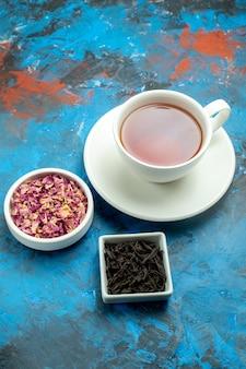 Vista inferior de uma xícara de chá em tigelas com pétalas de flores secas e chá na superfície azul vermelha