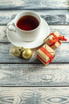 Vista inferior de uma xícara de chá, presentes, brinquedos para árvore de natal em fundo de madeira