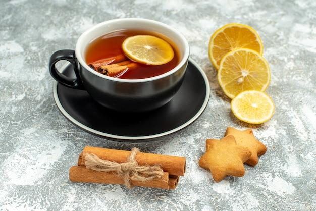 Vista inferior de uma xícara de chá, rodelas de limão, palitos de canela na superfície cinza