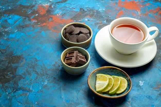 Vista inferior de uma xícara de chocolates de chá e rodelas de limão no espaço livre da superfície azul vermelha