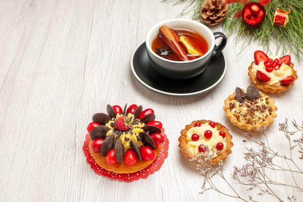 Vista inferior de uma xícara de tortas de bolo de baga de chá de canela e limão e folhas de pinheiro com brinquedos de natal no fundo branco de madeira