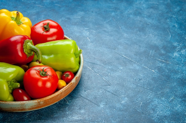 Vista inferior de vegetais de cores diferentes, pimentão, tomate, cereja, tomate, cereja, bandeja de madeira, mesa azul, com, espaço de cópia