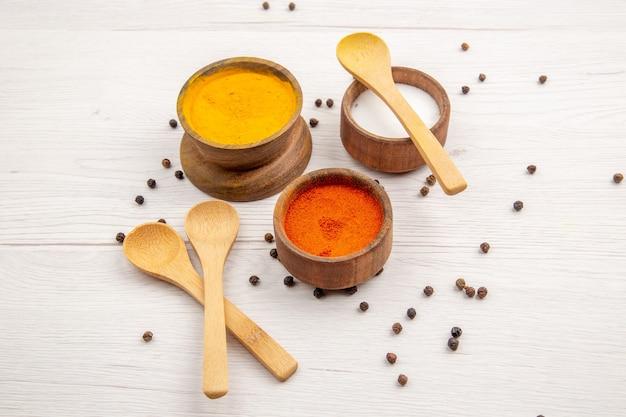 Vista inferior, diferentes especiarias, açafrão, pimenta vermelha, sal em pó em uma tigela pequena colheres de pau com pimenta preta espalhada na mesa cinza