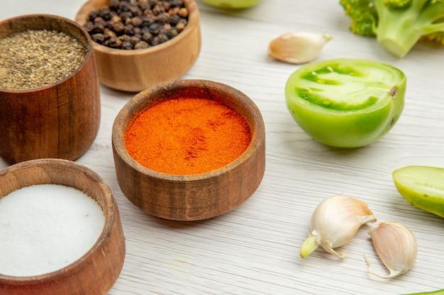 Vista inferior, diferentes especiarias em pequenas tigelas cortam tomates verdes e alho na mesa branca