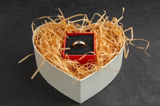Vista inferior do anel de noivado em caixa em forma de coração em fundo escuro