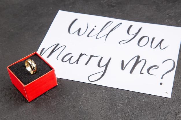 Vista inferior do anel de noivado em caixa vermelha, quer se casar comigo, escrito em papel em fundo escuro