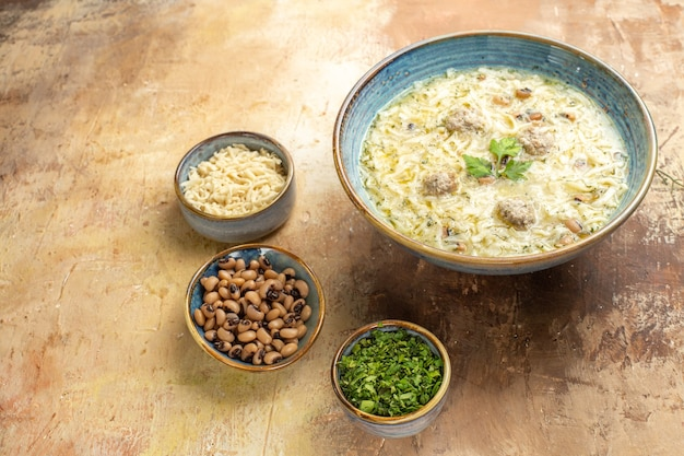 Vista inferior do azerbaijão erishte em uma tigela diferentes ingredientes em tigelas sobre fundo bege
